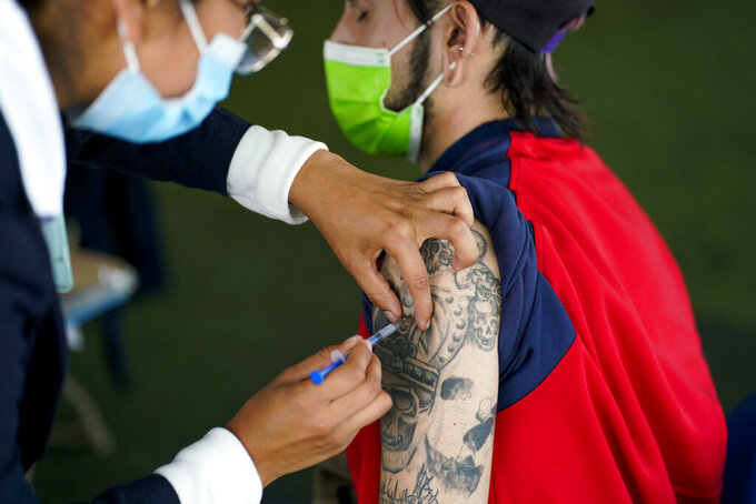 A healthcare worker injects a person with a dose of the Pfizer COVID-19, during a vaccination drive for people between the ages of 18-29, in Mexico City, Thursday, Aug. 19, 2021. (AP Photo/Eduardo Verdugo)