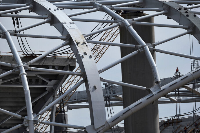 A construction worker stands amidst the towering roof over the new NFL Los Angeles Stadium while under construction in Inglewood, Calif. on Monday April 15, 2019. Stadium officials hosted a tour for the media after the final piece of the canopy structure to hold the roof was completed. (AP Photo/Richard Vogel)