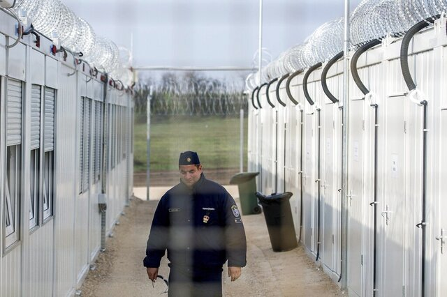 FILE - In this Thursday, April 6, 2017 file photo a Hungarian police officer patrols the enlarged transit zone set up for migrants at the Hungary's southern border with Serbia near Tompa, 169 kms southeast of Budapest, Hungary. Hungary's government says it is shutting down the transit zones on its southern border with Serbia where asylum-seekers are being kept while their asylum requests are decided. (Sandor Ujvari/MTI via AP, file)