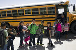 FILE - In this March 31, 2017, file photo, students board a school bus after class at Columbus Elementary School in Columbus, N.M.  New Mexico Public Education Department officials say, Monday, Sept. 28, 2021,  few grade-school students participated in state testing last year and that it is impossible to measure learning loss from the pandemic.  (AP Photo/Rodrigo Abd, File)