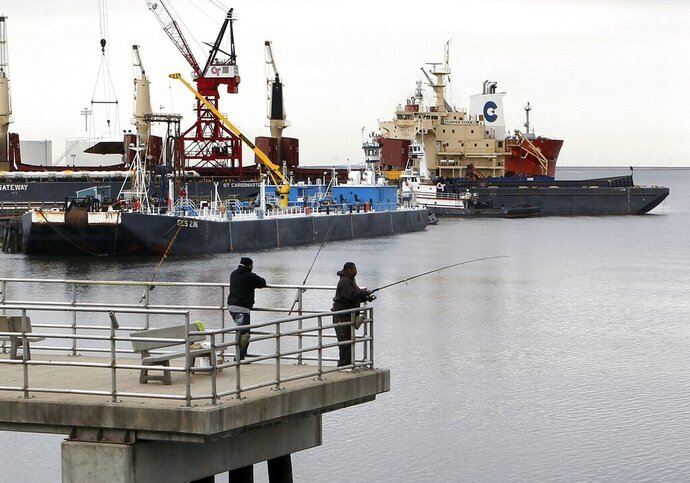 FILE - In this April 22, 2011 file photo, men fish from a pier in the Port of New Haven, Conn., as cargo vessels are docked at rear. Connecticut lawmakers have scheduled a forum on Tuesday, Aug. 20, 2019, to learn more about the finances and management practices at the Port Authority, which has come under scrutiny after paying a former board chairwoman's daughter $3,000 for office art. (AP Photo/Steven Senne, File)