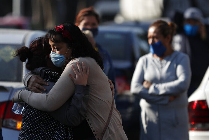 Family members of Gabriel Ulices Martinez Gutierrez, 38, who according to hospital staff is suspected to have died from complications of COVID-19, embrace outside San Nicolas Tolentino crematorium in the Iztapalapa district of Mexico City, Tuesday, May 5, 2020. Iztapalapa has the most confirmed cases of the new coronavirus within Mexico's densely populated capital, itself one of the hardest hit areas of the country with thousands of confirmed cases and around 500 deaths. (AP Photo/Rebecca Blackwell)
