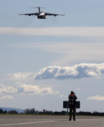 A photographer films a U.S. Air Force C-17 take off from Christchurch Airport in the season's first flight to McMurdo Station in Antarctica, Monday, Sept. 14, 2020. The first U.S. flight into Antarctica following months of winter darkness left from New Zealand Monday with crews extra vigilant about keeping out the coronavirus. (AP Photo/Mark Baker)
