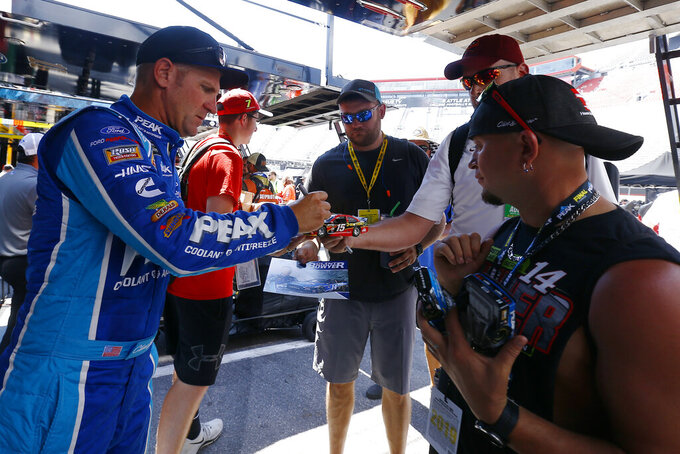 Driver Clint Bowyer signs autographs before practice for a NASCAR Cup Series auto race, Friday, Aug. 16, 2019, in Bristol, Tenn. (AP Photo/Wade Payne)