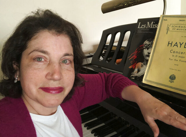 In this June 3, 2020, photo, Associated Press retail writer Anne D'Innocenzio sits at her piano in her apartment in New York. Her piano has been a source of comfort during the coronavirus outbreak. (AP Photo/Anne D'Innocenzio)