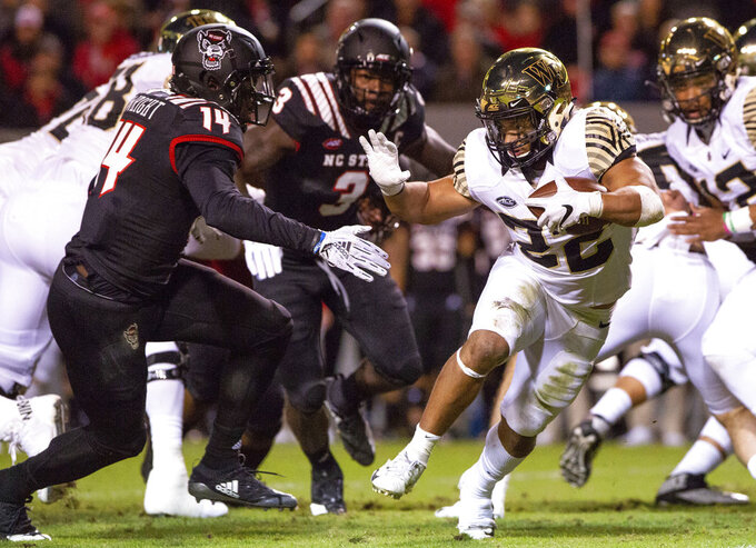 Wake Forest's Matt Colburn II (22) carries the ball as North Carolina State's Dexter Wright (14) looks to make a tackle during the first half of an NCAA college football game in Raleigh, N.C., Thursday, Nov. 8, 2018. (AP Photo/Ben McKeown)