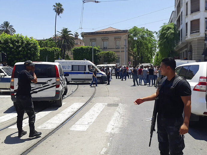 Tunisian police officers stands guard near an explosion site in Tunis, Thursday June 27, 2019. The Tunisian Interior ministry said one police officer has died in the suicide bombing targeting a police patrol in a busy commercial street in central Tunis. (AP Photo/Riadh Dridi)