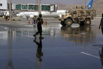 A Taliban soldier walks on the tarmac near parked planes at Hamid Karzai International Airport in Kabul, Afghanistan, Sunday, Sept. 5, 2021. Some domestic flights have resumed at Kabul's airport, with the state-run Ariana Afghan Airlines operating flights to three provinces. (AP Photo/Wali Sabawoon)