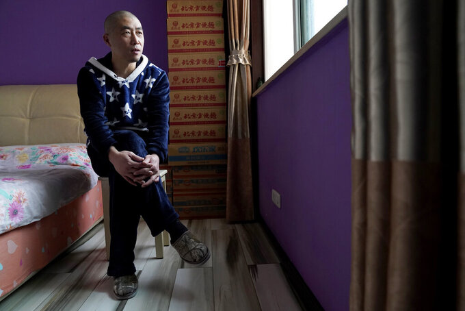 Wuhan resident Zhu Tao speaks during an interview near boxes of instant noodles stacked in his bedroom at home in Wuhan in central China's Hubei province on Wednesday, Oct. 21, 2020. Zhu, a government critic, took precautions against the virus early and felt vindicated when the outbreak exploded and the city went into lockdown. But now that the situation is back to something close to normal in Wuhan, Zhu finds himself at odds with his neighbors and the government. (AP Photo/Ng Han Guan)
