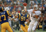 FILE - In this Dec. 15, 1986, file photo, Miami Dolphins' quarterback Dan Marino, right, is pressured by Los Angeles Rams' Kevin Greene during an NFL football game in Anaheim, Calif. Hall of Fame linebacker Greene, considered one of the fiercest pass rushers in NFL history, has died. He was 58. Greene died Monday, Dec. 21, 2020, the family confirmed, as did the Pro Football Hall of Fame. (AP Photo/Rod Boren, File)