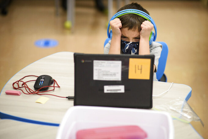 First-grader Kayden Welch gets frustrated with his computer during the first day back to in-person learning at Cliffdale Elementary School in Fayetteville, N.C., on Monday, March 15, 2021. Students last went to school buildings for classes on March 13, 2020. (Andrew Craft /The Fayetteville Observer via AP)