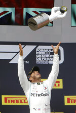Mercedes driver Lewis Hamilton, of Britain, celebrates on the podium after winning the French Formula One Grand Prix, at the Paul Ricard racetrack, in Le Castellet, southern France, Sunday, June 23, 2019. (AP Photo/Claude Paris)
