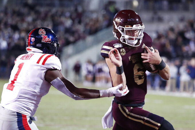 Mississippi State quarterback Garrett Shrader (6) dodges Mississippi linebacker Lakia Henry (1) on his way to a 1-yard touchdown run during the first half of an NCAA college football game in Starkville, Miss., Thursday, Nov. 28, 2019. (AP Photo/Rogelio V. Solis)