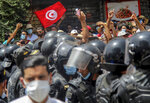 Protesters face Tunisian police officers during a demonstration in Tunis, Tunisia, Sunday, July 25, 2021. Violent demonstrations broke out on Sunday in several Tunisian cities as protesters expressed anger at the deterioration of the country's health, economic and social situation. (AP Photo/Hassene Dridi)