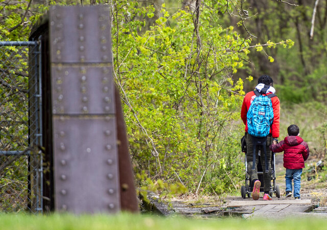 In this April 20, 2020 photo, A person walks with a little boy across the trestle near tent city off of Martin Luther King Jr Dr. in Allentown, Pa. Allentown's homeless have yet to see an outbreak, but the population, now mostly on the streets or in encampments, is not ready for when that happens, advocates say.(April Gamiz/The Morning Call via AP)