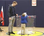 A man lets his son help him cast his ballot in elections to the Polish parliament in Warsaw, Poland, on Oct. 13, 2019. Poles are voting Sunday in a parliamentary election, that the ruling party of Jaroslaw Kaczynski is favored to win easily, buoyed by the popularity of its social conservatism and generous social spending policies. Critics, however, fear that another term for the party, whose term has included an erosion of the rule of law, will mark a further decline in democracy. (AP Photo/Czarek Sokolowski)