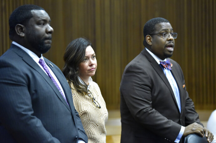 FILE -- In a November 12, 2019 file photo, Allegheny (PA) County Controller Chelsea Wagner stands with co-council Kevin Mincey, left, and Charles Longstreet, II, during her trial in front of Judge Dalton A. Roberson.  A jury has acquitted Wagner of disturbing the peace but couldn't reach a verdict on a felony charge of obstructing police at a Detroit hotel.  (Todd McInturf/Detroit News via AP)