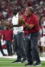 Arkansas head coach Sam Pittman, front, instructs his team in the second half of an NCAA college football game against Texas A&M in Arlington, Texas, Saturday, Sept. 25, 2021. (AP Photo/Tony Gutierrez)