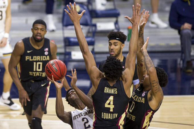 Notre Dame's Trey Wertz (2) takes a shot with pressure from Florida State's Malik Osborne (10), Scottie Barnes (4), Anthony Polite and RayQuan Evans (0) during the second half of an NCAA college basketball game Saturday, March 6, 2021, in South Bend, Ind. Notre Dame won 83-73. (AP Photo/Robert Franklin)