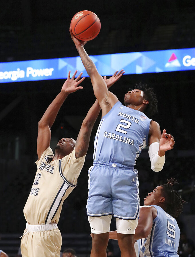 Georgia Tech forward Khalid Moore loses the rebound battle with North Carolina guard Caleb Love during an NCAA college basketball game Wednesday, Dec. 30, 2020, in Atlanta. (Curtis Compton/Atlanta Journal-Constitution via AP, Pool)