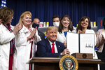 President Donald Trump holds up a signed executive order on lowering drug prices, in the South Court Auditorium in the White House complex, Friday, July 24, 2020, in Washington. (AP Photo/Alex Brandon)