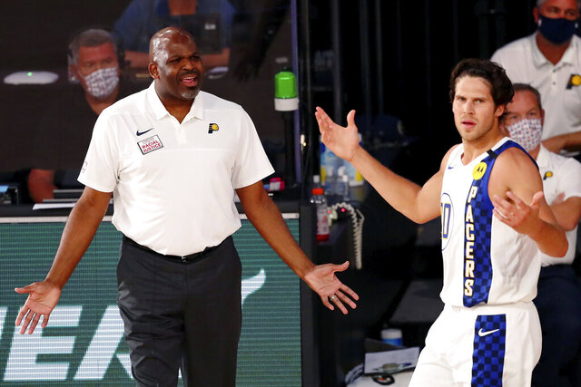Indiana Pacers head coach Nate McMillan and forward Doug McDermott (20) react to a call during the second half of an NBA basketball game against the Miami Heat, Monday, Aug. 10, 2020, in Lake Buena Vista, Fla. (Kim Klement/Pool Photo via AP)