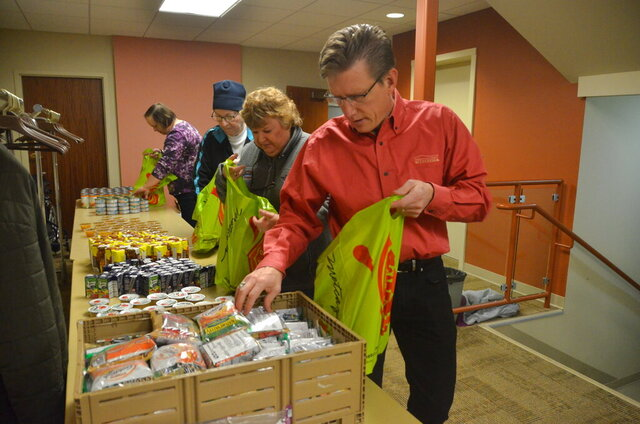 In this Friday, Dec. 13, 2019, photo, American Family Insurance agent Brad Bodden and a group of volunteers pack 50 food bags at Westminster Presbyterian Church to put in Thoreau Elementary School students' lockers, providing meals and snacks for the weekend, in Madison, Wis. (Scott Girard/The Capital Times via AP)