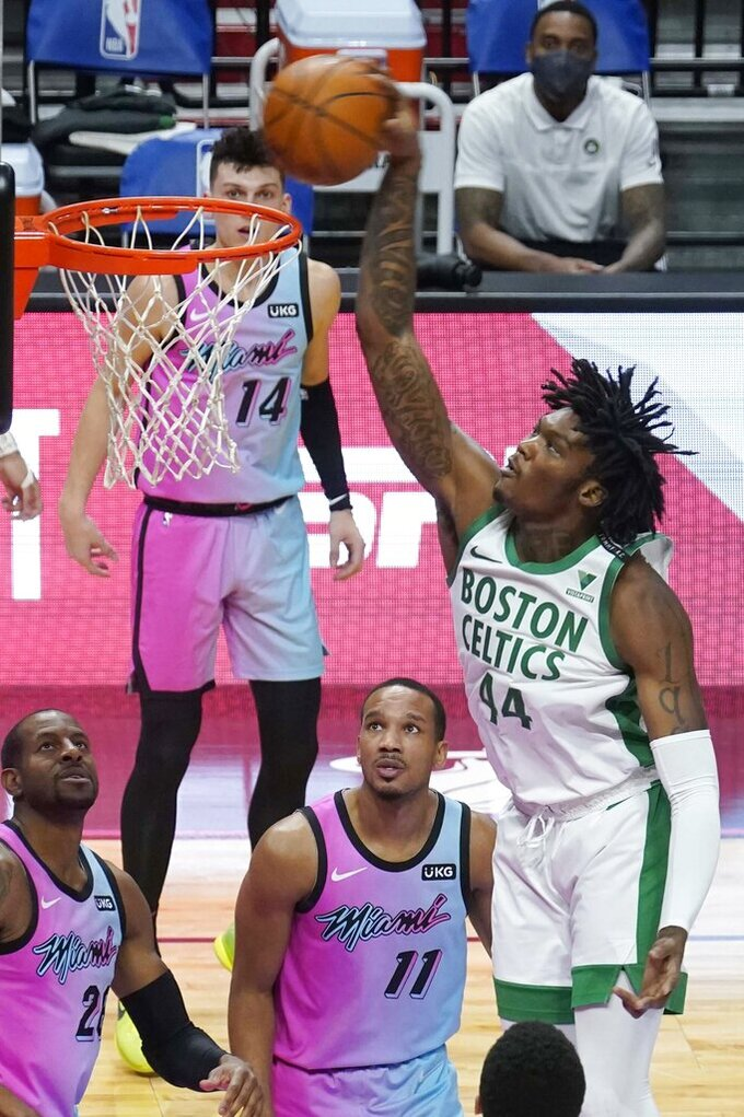 Boston Celtics center Robert Williams III (44) dunks the ball over Miami Heat guards Avery Bradley (11) and Andre Iguodala (28) during the second half of an NBA basketball game, Wednesday, Jan. 6, 2021, in Miami. (AP Photo/Marta Lavandier)