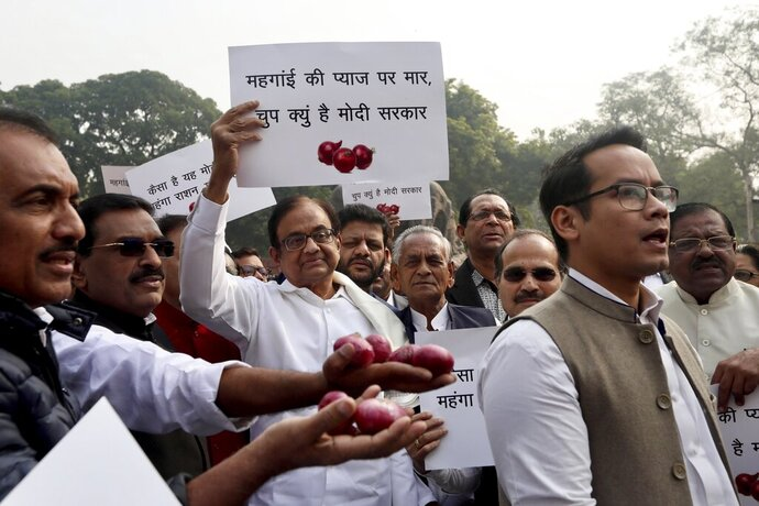 Indian lawmaker and former Finance Minister Palaniappan Chidambaram, center, holds a placard that reads