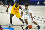 Michigan guard Mike Smith (12) drives on Maryland guard Darryl Morsell (11) in the second half of an NCAA college basketball game at the Big Ten Conference tournament in Indianapolis, Friday, March 12, 2021. (AP Photo/Michael Conroy)