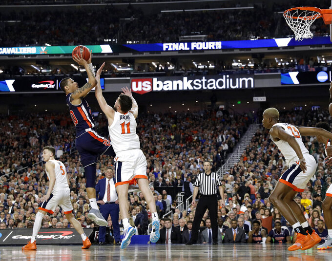 Auburn guard Samir Doughty, left, shoots over Virginia guard Ty Jerome (11) during the second half in the semifinals of the Final Four NCAA college basketball tournament, Saturday, April 6, 2019, in Minneapolis. (AP Photo/Jeff Roberson)