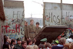 FILE - In this Nov. 11, 1989 file photo, East German border guards are seen through a gap in the Berlin wall after demonstrators pulled down a segment of the wall at Brandenburg gate, Berlin. (AP Photo/Lionel Cironneau, File)