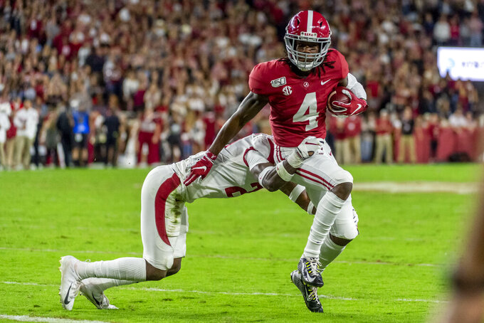 Alabama wide receiver Jerry Jeudy (4) eludes Arkansas defensive back Montaric Brown (21) to break free for a touchdown reception during the first half of an NCAA college football game, Saturday, Oct. 26, 2019, in Tuscaloosa, Ala. (AP Photo/Vasha Hunt)