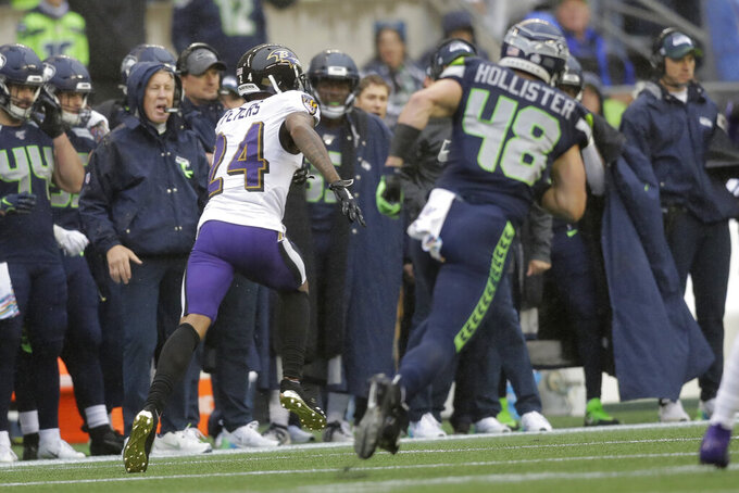 Baltimore Ravens cornerback Marcus Peters (24) runs for a touchdown as Seattle Seahawks tight end Jacob Hollister pursues after Peters intercepted a pass during the first half of an NFL football game, Sunday, Oct. 20, 2019, in Seattle. Peters ran for a touchdown on the play. (AP Photo/John Froschauer)