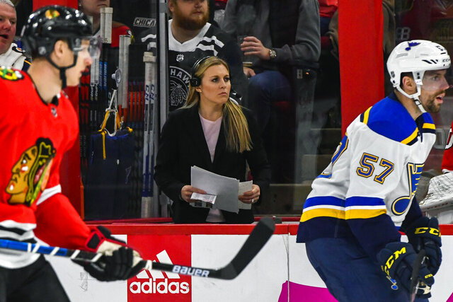 """FILE - In this March 8, 2020, file photo, broadcast team member Kendall Coyne Schofield works during the first period of an NHL hockey game between the Chicago Blackhawks and the St. Louis Blues, in Chicago. The Professional Women's Hockey Players Association enters its second season with plans to regionalize its structure by basing players in five hub cities, while also continuing its Dream Gap Tour series of barn-storming stops across North America. """"The new structure provides players with a more professional training environment on a regular basis, which will allow us to put the best product of women's professional hockey on the ice daily,"""" two-time U.S. Olympian and PWHPA board president Kendall Coyne Schofield said in a released statement. (AP Photo/Matt Marton, File)"""