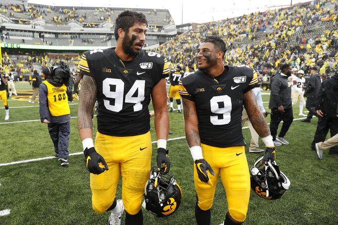 Iowa defensive end A.J. Epenesa (94) walks off the field with teammate Geno Stone (9) after an NCAA college football game against Purdue, Saturday, Oct. 19, 2019, in Iowa City, Iowa. Iowa won 26-20. (AP Photo/Charlie Neibergall)