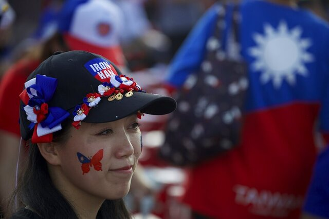 A supporter of Han Kuo-yu, Taiwan's 2020 presidential election candidate for the KMT or Nationalist Party, wearing the colors of the Taiwan flag, waits for the start of a campaign rally in southern Taiwan's Kaohsiung city on Friday, Jan 10, 2020. Taiwan will hold its presidential election on Jan. 11, 2020. (AP Photo/Ng Han Guan)