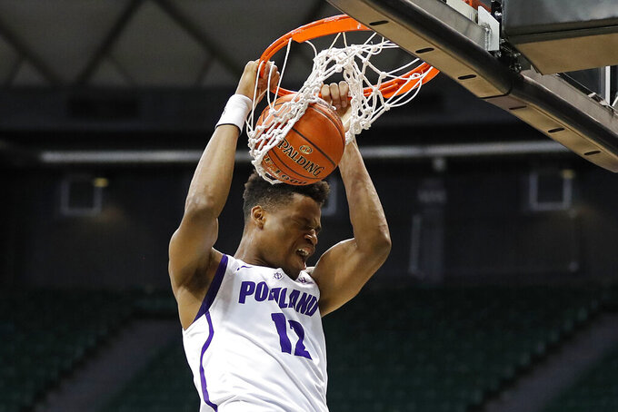 Portland center Theo Akwuba (12) dunks during the first half of the NCAA college basketball game against Houston Sunday, Dec. 22, 2019, in Honolulu. (AP Photo/Marco Garcia)
