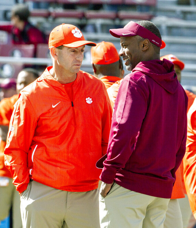Clemson head coach Dabo Swinney, left, and Florida State head coach Willie Taggart talk at midfield prior to an NCAA college football game in Tallahassee, Fla., Saturday, Oct.27, 2018. (AP Photo/Mark Wallheiser)