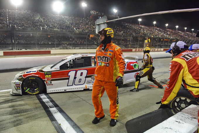 A member of Kyle Busch's team watches while Busch exits from a pit stop during a NASCAR Cup Series auto race on Sunday, Sept. 1, 2019, at Darlington Raceway in Darlington, S.C. (AP Photo/Richard Shiro)