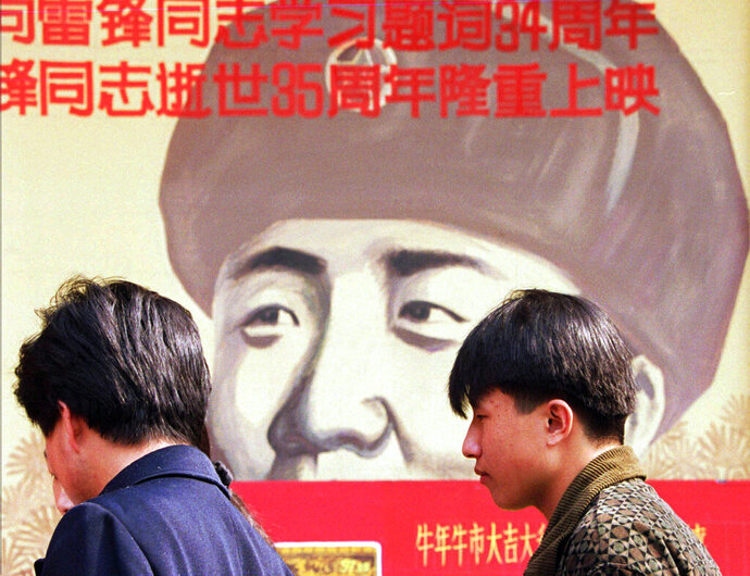 """CAPTION CORRECTION CORRECTS OPENING DAY: FILE - In this March 5, 1997, file photo, Chinese wait outside a movie theater featuring a poster promoting a movie about Lei Feng, a soldier in the 1960's who was promoted to hero and model soldier status by Chinese authorities, in Beijing. The official Xinhua News Agency said the company launched its first """"Lei Feng Spirit"""" restaurant in Lei's home province of Hunan on Sunday, ahead of Tuesday's official remembrance day for the soldier who died in 1962 at the age of 21. (AP Photo/Greg Baker, File)"""
