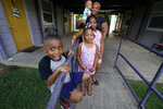Brianne Epps of Jackson, Miss., 28, background, is a single mother with sons Micah Epps, 4, in front, and Nolan Epps, 11 months in her arms and daughters Laila Barnes, 6, second from left, and Kaylee Barnes, 8, center, outside her apartment complex in Jackson, Miss., Wednesday, July 21, 2021. Epps earns $9 an hour working with infants and toddlers in a childcare center, but she has a bigger dream of operating a soul food catering business. (AP Photo/Rogelio V. Solis)