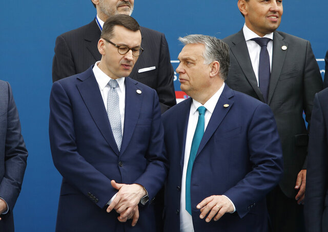 FILE - In this Feb. 1, 2020 file photo, Poland's Prime Minister Mateusz Morawiecki, left, and Hungary's Prime Minister Victor Orban share a word as they line up for a group picture prior to a meeting in Beja, Portugal. Polish government officials insisted on Friday, Dec. 4, 2020, that they are sticking to their tough negotiating position ahead of a key European Union summit next week that should finalize the bloc's next seven-year budget and a major pandemic recovery package. (AP Photo/Armando Franca, File)