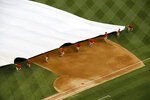 Grounds crew members pull a tarp over the infield during a rain delay before a baseball game between the Philadelphia Phillies and the Washington Nationals, Tuesday, June 18, 2019, in Washington. (AP Photo/Patrick Semansky)