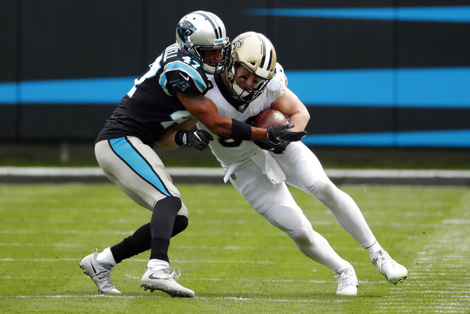 Carolina Panthers defensive back Ross Cockrell (47) tackles New Orleans Saints tight end Josh Hill during the first half of an NFL football game in Charlotte, N.C., Sunday, Dec. 29, 2019. (AP Photo/Gerry Broome)