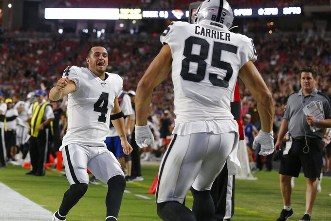 Oakland Raiders tight end Derek Carrier (85) celebrates his touchdown against the Arizona Cardinals with quarterback Derek Carr (4) during the first half of an an NFL football game, Thursday, Aug. 15, 2019, in Glendale, Ariz. (AP Photo/Rick Scuteri)