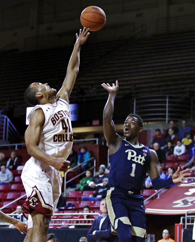 Boston College forward Steffon Mitchell (41) reaches to block as Pittsburgh guard Xavier Johnson (1) lofts a shot high during the first half of an NCAA college basketball game in Boston, Tuesday, Feb. 12, 2019. (AP Photo/Charles Krupa)