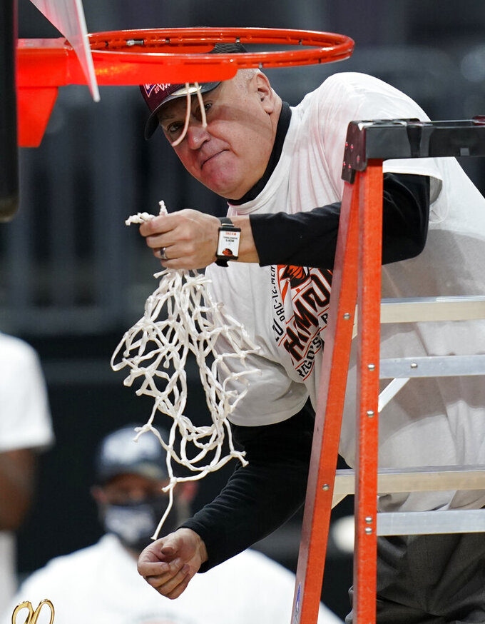 Oregon State head coach Wayne Tinkle cuts down the net after his team defeated Colorado in an NCAA college basketball game in the championship of the Pac-12 men's tournament Saturday, March 13, 2021, in Las Vegas. (AP Photo/John Locher)