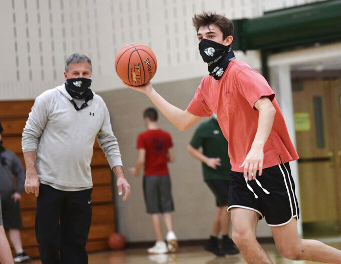 North Star High School senior Noah Solarczyk, right, performs a drill as head coach Randy Schrock looks on during varsity basketball practice in Boswell, Pa., Monday, Dec. 7, 2020. Schools in the PIAA WestPAC conference, like North Star, are making their own decisions about participating in extracurricular activities during the Covid-19 outbreak. (John Rucosky/Tribune-Democrat via AP)