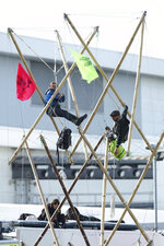 Two protesters attached to bamboo and two sitting on the roof of a van block the road, outside Broxbourne newsprinters, in Broxbourne, Hertfordshire, England, Saturday, Sept. 5, 2020. Environmental activists have blockaded two British printing plants, disrupting the distribution of several national newspapers. The group Extinction Rebellion said it targeted printworks at Broxbourne, north of London, and Knowsley in northwest England that are owned by Rupert Murdoch's News Corp. Dozens of protesters locked themselves to vehicles and bamboo scaffolding to block the road outside the plants. The facilities print Murdoch-owned papers The Sun and The Times, as well as the Daily Telegraph, the Daily Mail and the Financial Times. (Yui Mok/PA via AP)